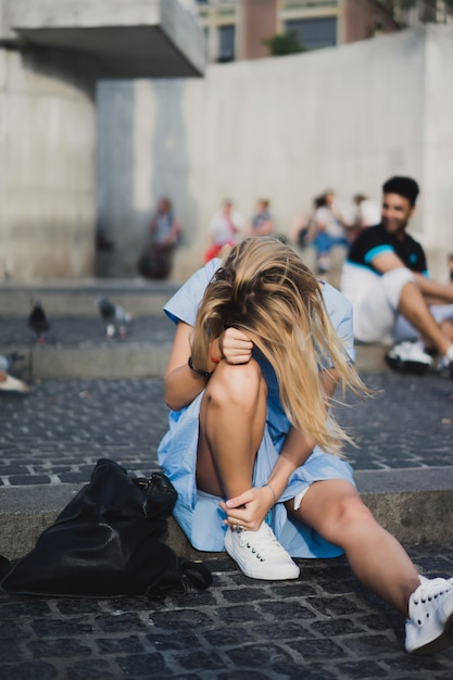 A girl is sitting on dam square. amsterdam. Free Photo