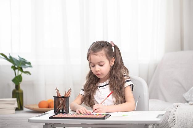 La ragazza è seduta al tavolo e fa i compiti. Foto Gratuite