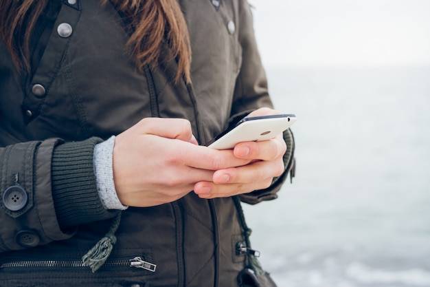 Girl in jacket uses a smartphone while walking along the beach Premium Photo