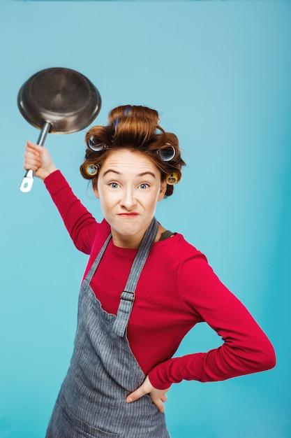 Девушка шутит с сковородой в руках, делая еду Бесплатные Фотографии