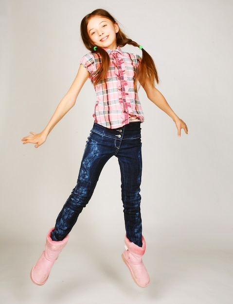 Girl jumps on a gray background Premium Photo