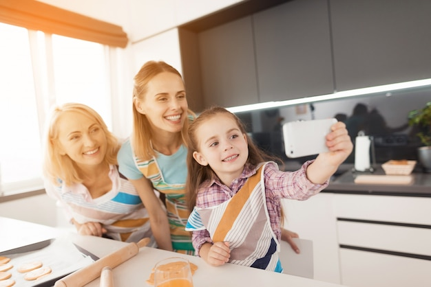 Girl in kitchen makes selfie with her mother and grandmother Premium Photo