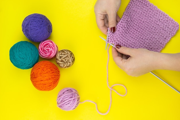 The girl knits a children's scarf on a yellow background Premium Photo
