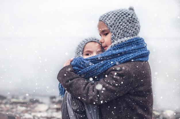 Girl in knitted grey hat hugging her frozen smaller brother Premium Photo