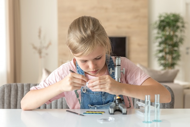 Girl learning chemistry playing with the microscope at home Premium Photo