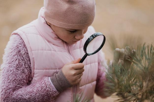돋보기로 자연 속에서 과학을 배우는 소녀 무료 사진