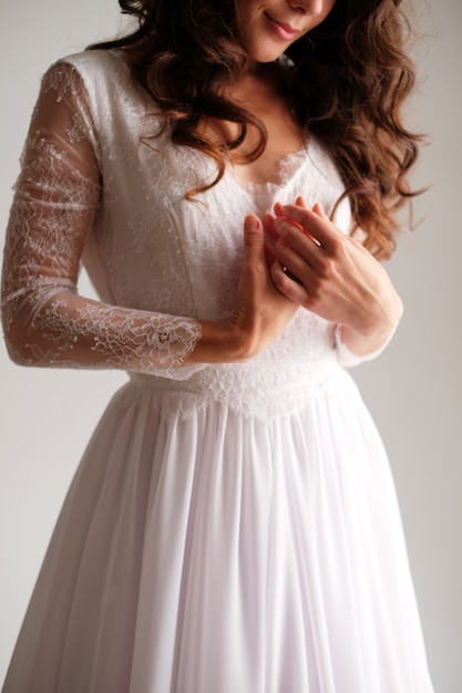 A girl in a light dress folded her arms across her chest. hands of the bride gently pink dress Premium Photo