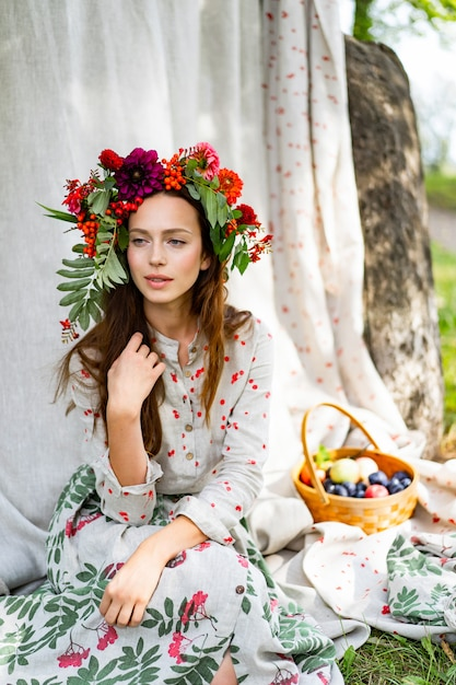 Girl in a linen dress. with a wreath of flowers on her ...