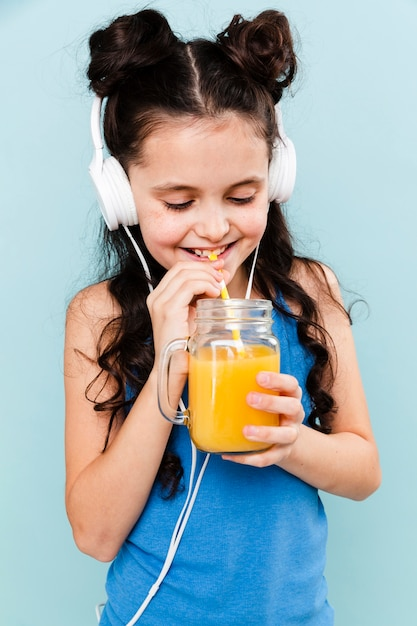 Girl listening music and drinking juice Free Photo