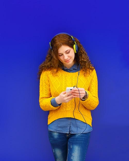 Girl listening to music in headphones with smartphone Premium Photo