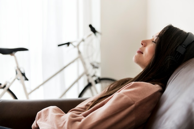 Girl listening to music at home on the sofa Free Photo