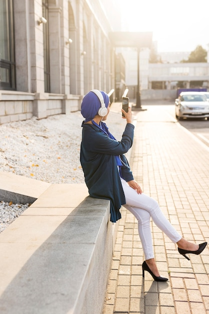 Girl listening to music through headphones outside with copy space Free Photo