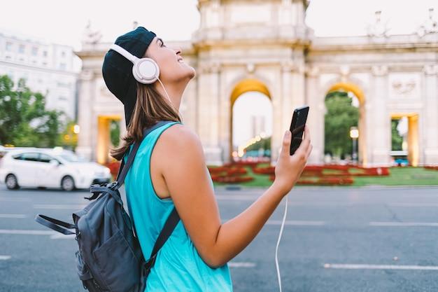 Девушка слушает музыку перед пуэрта-де-алькала в мадриде Premium Фотографии