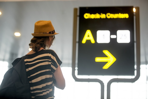 Girl looking at airport information board Free Photo