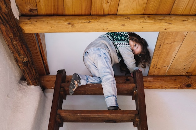 Girl looking at camera while climbing ladder Free Photo