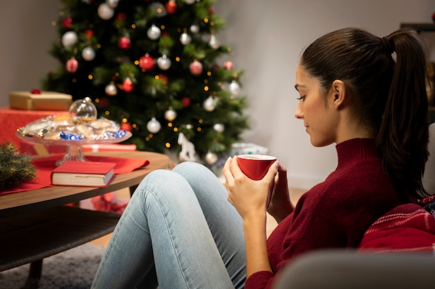 Girl looking at a cup with a christmas background Free Photo