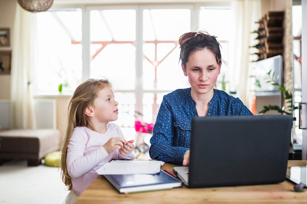 Girl looking at her mother working on laptop over wooden desk Free Photo