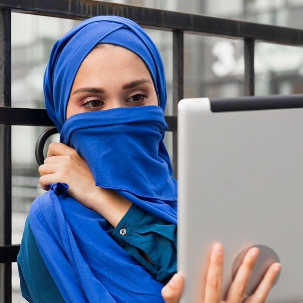 Girl looking at her tablet while covering her mouth with a hijab Free Photo