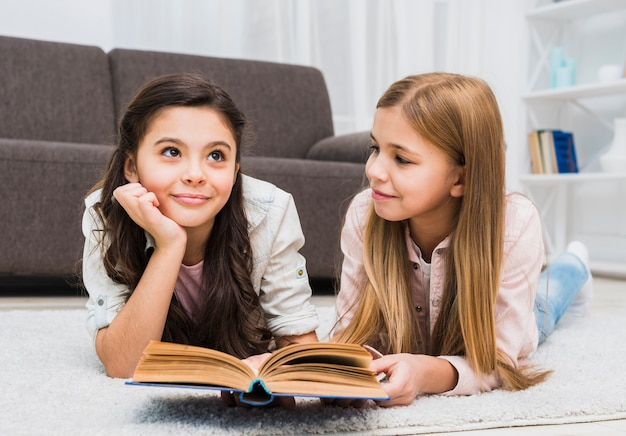 Girl looking at her thoughtful friend while reading book in the living room Free Photo