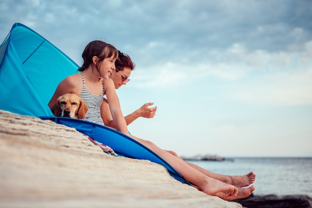 Girl looking into sunset while sitting in beach tent with mother and dog Premium Photo