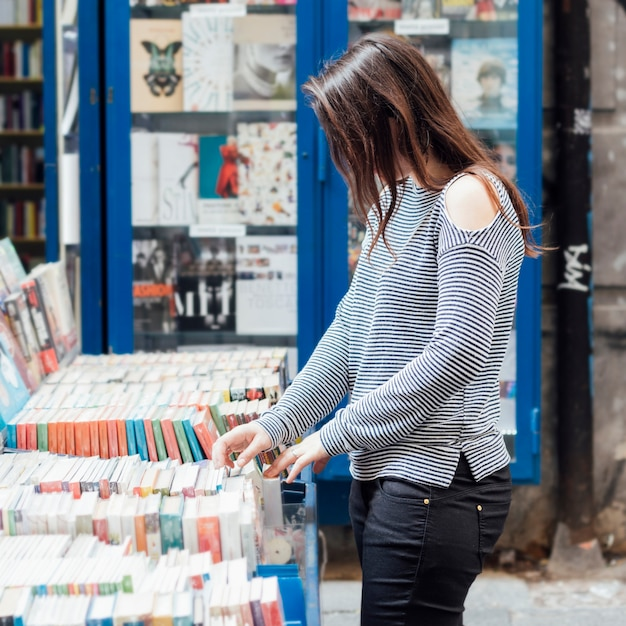 Girl looking for old books Free Photo