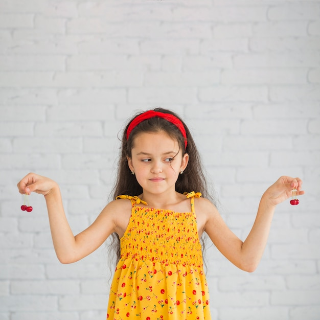 Girl looking at red cherries holding in her hands Free Photo