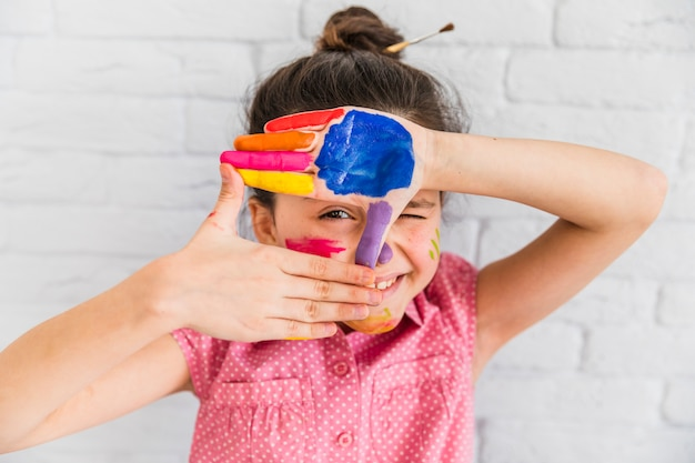 Girl looking through finger frame with paints on palm against white brick wall Free Photo