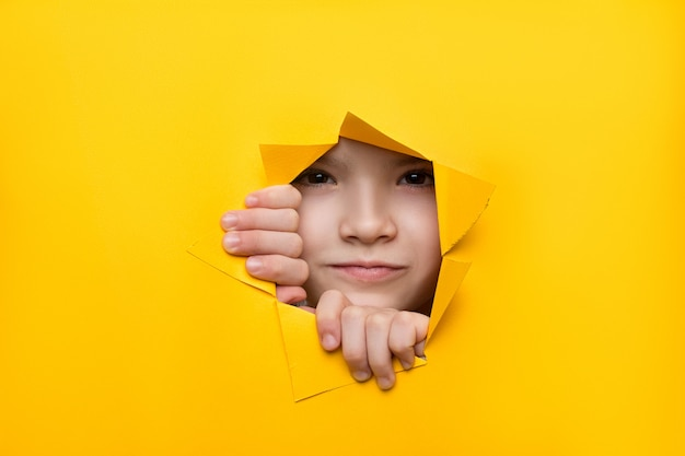 Girl looking through a hole in colored paper Premium Photo