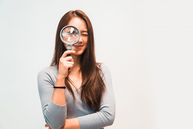 Girl looking through a magnifying glass Premium Photo