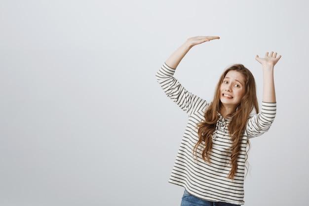 Girl looking uncomfortable as holding something big Free Photo
