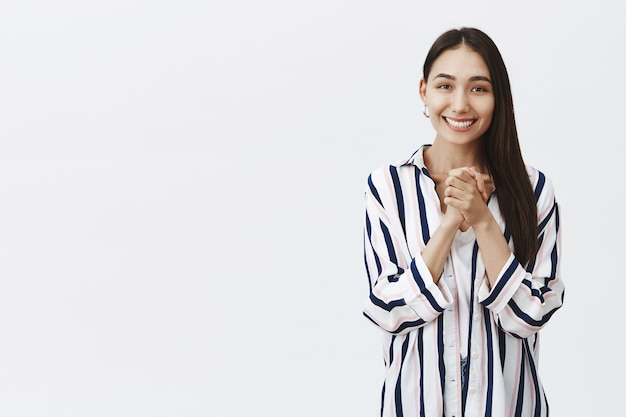 Girl looking with caring and admirable eyes, being thrilled and charmed with pleasant gift, clasping hands over chest and smiling with happiness, standing in striped blouse over gray wall Free Photo