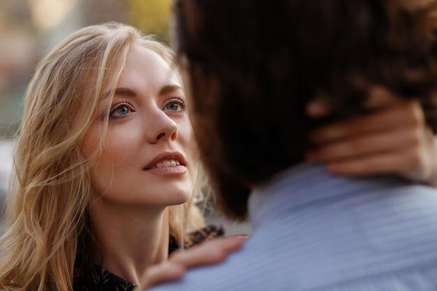 女の子は恋に男を見ています。カップル。クローズアップの肖像画。背景をぼかした写真 Premium写真