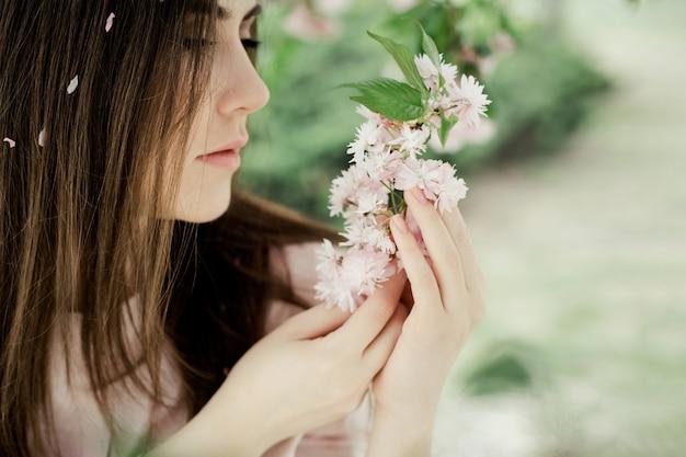 Girl looks at sakura branch in the park Free Photo