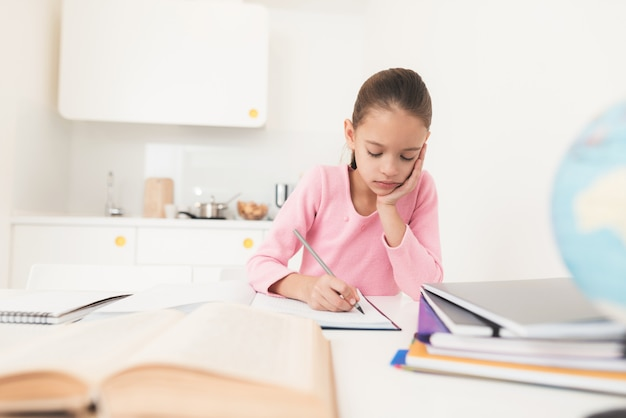 Girl looks thoughtfully into the textbook. Premium Photo