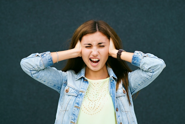 The girl, loudly, closed her ears with her hands Premium Photo