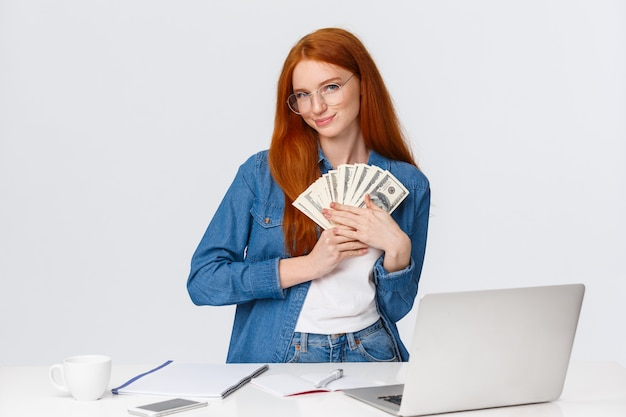 Девушка любит деньги, чувствует тепло денег в руках, стоит глупо и в восторге, получает зарплату и ухмыляется, ходит по магазинам онлайн, делает заказ в интернете, стоит возле ноутбука, белая стена Premium Фотографии