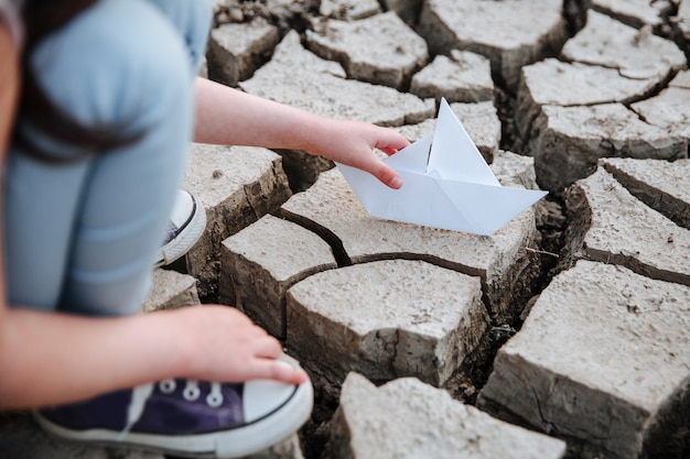 The girl lowers the paper boat onto the dry, cracked ground. Premium Photo
