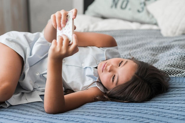 Girl lying on bed using smart phone Free Photo