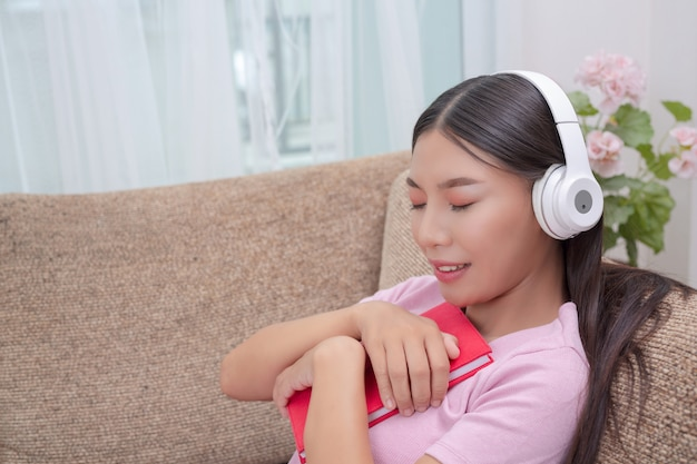 Girl lying on the couch listening to music and reading books  Photo