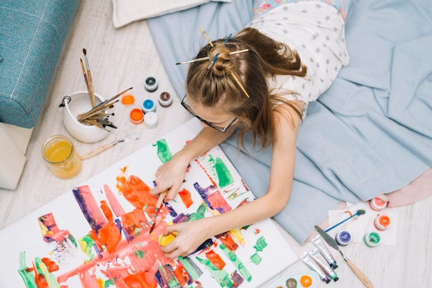 Girl lying on floor and painting with gouache Free Photo