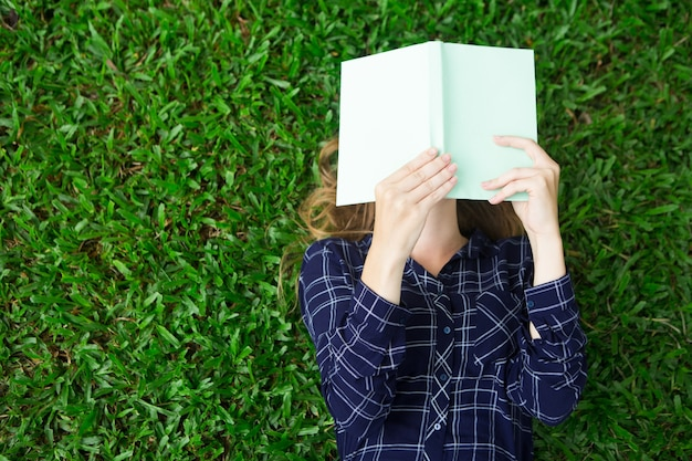 Girl Lying on Grass and Reading Book Free Photo