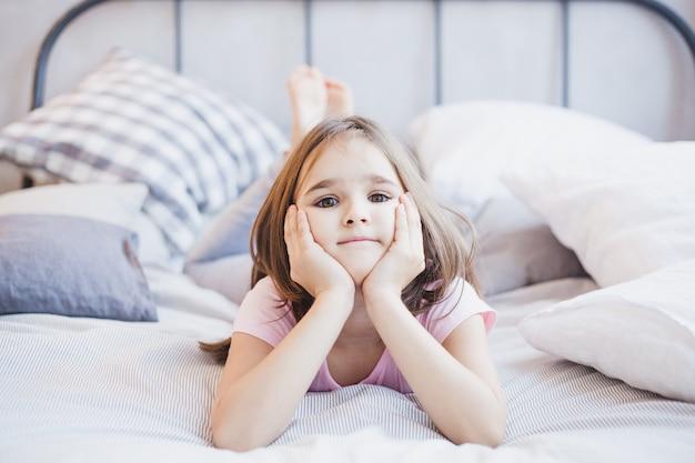 Прелестная дева в колье лежит на кровати