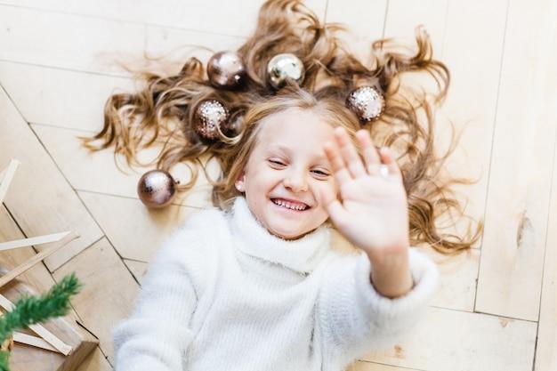 クリスマスツリーの彼女の髪のボールで床に横たわった少女 Premium写真