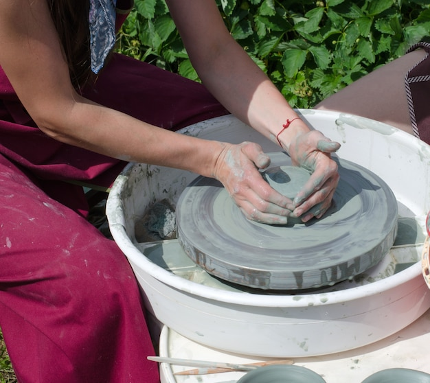 The girl makes a pot of clay on a potter's wheel. Premium Photo