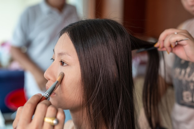 Girl makeup by using a professional makeup artist. Free Photo