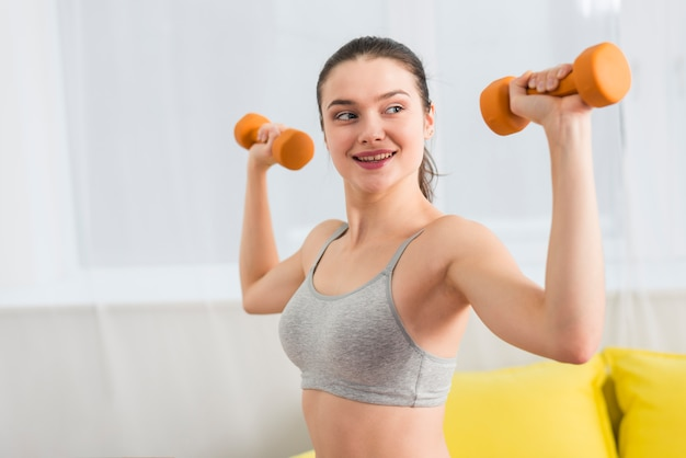 Girl making exercise with dumbbell in her house Free Photo