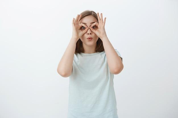 Девушка корчит рожи, теряя время. портрет игривой и радостной незрелой симпатичной женщины в футболке, которая делает круги над глазами руками, как будто смотрит в очки, складывая губы, дурачится Бесплатные Фотографии