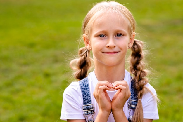Girl making a heart with her hands Free Photo