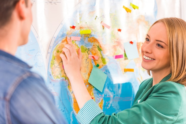 Girl and man look at each other on a map. Premium Photo