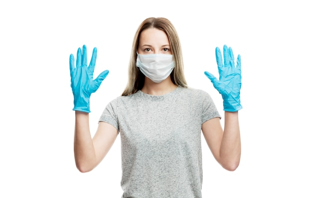 A girl in a medical mask and blue gloves raised her hands up. precautions during coronavirus rendezvous. isolated on a white wall. Premium Photo
